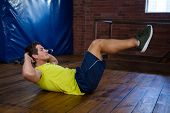 Determined man performing crunches in fitness studio poster
