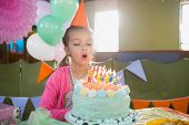 Birthday girl blowing birthday candles at home poster