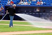 PORT ST. LUCIE, FLORIDA - MARCH 24: The head grounds keeper for the New York Mets waters the field d