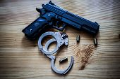 Black Pistol Gun With Silver Handcuffs And Golden Bullet Shells Laying On A Wooden Background Used B poster