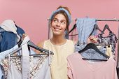 Woman Shopaholic Being In Boutique Choosing Many Outfits, Looking With Dreamy Expression Up, Not Kno poster