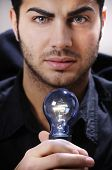 Young Man With Light Bulb In His Hands
