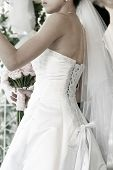 back and side bride on her wedding day with detailing on the lace ribbon back