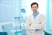 Young male dentist in light office poster