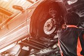 Car Lifted In Automobile Service For Fixing. Professional  Mechanic Male In Garage Automobile Checki poster