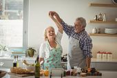 Senior couple dancing in kitchen at home poster