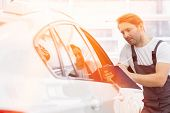 Automobile mechanic writing on clipboard while examining car in repair shop poster