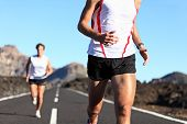 Running Sport. Runners on road in endurance run outdoors in beautiful landscape. closeup of man legs