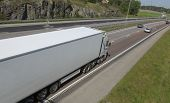 white truck, lorry on highway, leaning wide-view