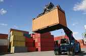 forklift truck moving containers in a busy commercial port