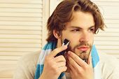 Man Holds Razor And Starts Shaving His Beard poster