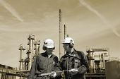engineers in front of large oil refinery, background in toning concept