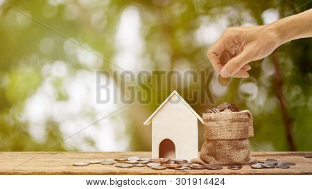 poster of Saving Money, Home Loan, Mortgage, A Property Investment For Future Concept. A Man Hand Putting Mone