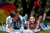 Father And Daughter Are Lying On The Blanket In The Park.family Having Picnic. Father Is Looking At  poster