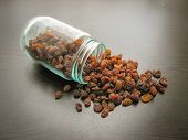 Brown Raisins Seamless Are Poured From A Glass Jar On Brown Wooden Surface. Brown Raisins Seamless I poster