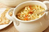 Chicken noodle soup in cream colored ceramic bowl with handles.  Plate of crackers and soup tureen i