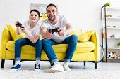Excited Father And Son Playing Video Game On Couch In Living Room poster