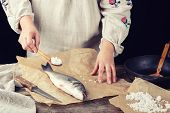 Fresh Whole Sea Bass Fish Lying On Brown Paper, Girl In A Gray Long Linen Dress Holds A Full Spoonfu poster