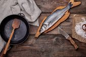 Fresh Whole Sea Bass Fish On A Brown Board, Next To It Is An Empty Round Black Frying Pan On A Woode poster