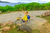Happy Caucasian Lifestyle Tourist Woman On Bicycle Near Anse Banane In La Digue, Seychelles, With Al poster