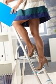 Pretty office assistant in short skirt standing on ladder, organizing file folder.?