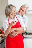 Happy senior Couple in Küche mit Glas Rotwein