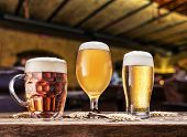 Glasses of beer on the wooden table. Blurred pub interior at the background. Assortment of beer. poster