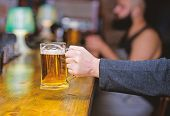 Beer Mug On Bar Counter Defocused Background. Glass With Fresh Lager Draft Beer With Foam. Male Hand poster