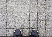 Top View On Sneakers And Square Sidewalk Pavement Background - Top Down View From Above On Sport Sho poster