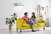 Happy Young Couple Talking And Holding Cups While Sitting On Yellow Sofa Under Air Conditioner At Ho poster