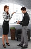 Businesswoman dictating to assistant, standing in office, assistant taking notes.?
