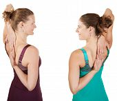 picture of shoulder-blade  - Two fit women stretching shoulders over white background - JPG