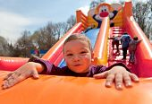 stock photo of inflatable slide  - Smiling little boy playing on inflatable slide - JPG