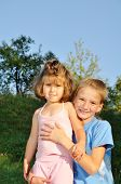 Two little girls standing together in the park, one holds another