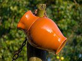 foto of loamy  - Ceramic jug on the tree in a village - JPG