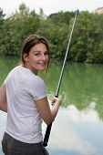 picture of fisherwomen  - Brunette Woman Fishing at a lake with green water - JPG