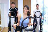 picture of vibration plate  - Group of two men and one woman on a vibration massage plate in a gym