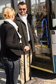 Woman and man talking in bus station smiling commuters journey