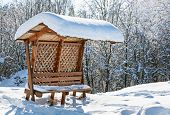 Wooden awning bench covered by hard snow