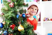 Little boy in Santa hat peeks out from behind Christmas tree