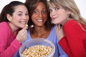 stock photo of peppy  - Peppy women eating popcorn - JPG