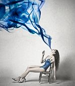 Beautiful woman exhales a blue smoke