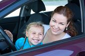 Happy Toothy Smiling Mother With Small Daughter On Driver Seat Inside Of Car