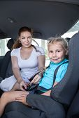 Mother Helping Daughter To Fasten Car Safety Belt In Restraint Seat