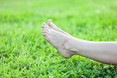 Bare Feet Laying On Green Grass Background