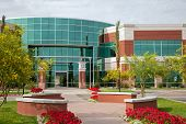 pic of building exterior  - Office building with glass panels flowers and trees - JPG