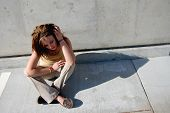 Teenage Girl Sitting On Concrete