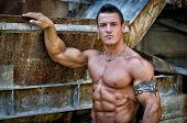 Handsome Young Muscle Man With Hand On Rusty Metal Structure