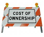 The words Cost of Ownership on a barricade to illustrate the prohibitive true price of a car, home o