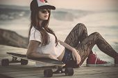 stock photo of skate  - Beautiful and fashion young woman posing with a skateboard - JPG